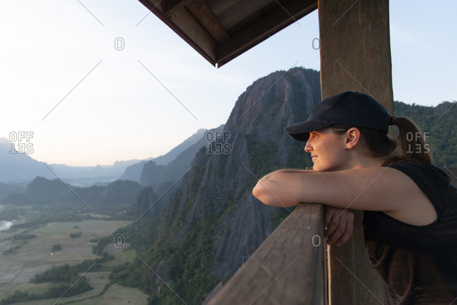 Female hiker gazing over a valley from the top of a mountain near Vang Vieng, Laos