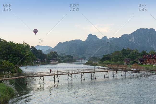 Vang Vieng, Laos - November 24, 2014: Hot air balloon over a bridge on the Nam Song River
