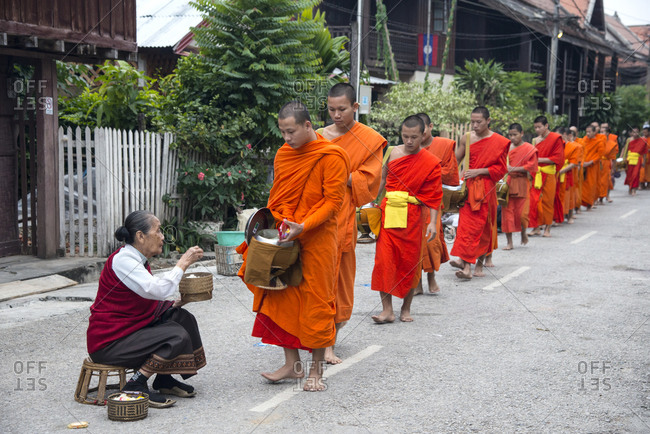 Luang Prabang, Laos - November 25, 2014: Buddhist monks receive a portion of sticky rice from a disciple during an early morning daily ritual known as Sai Bat (morning alms)