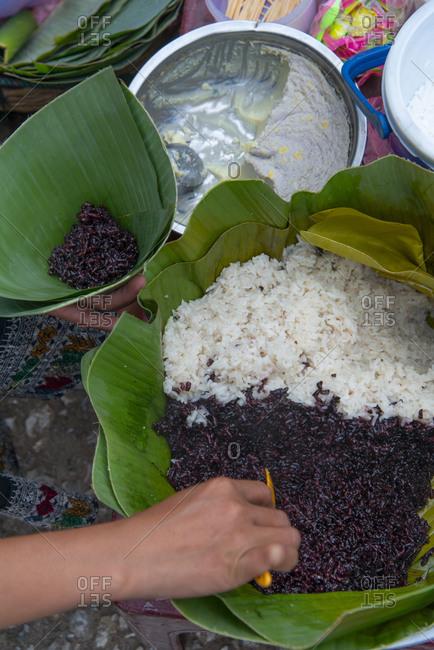 Vendor making cones of rice at a market in Luang Prabang, Laos