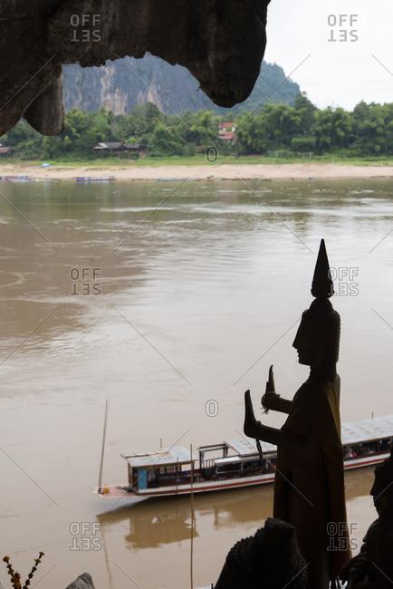 Buddha figures in silhouette at Pak Ou Caves near Luang Prabang, Laos