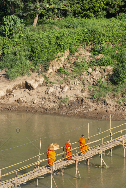 Buddhist monks crossing a river in Luang Prabang, Laos