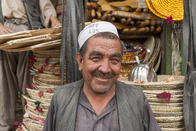 Afghanistan - June 11, 2011: Portrait of a senior man in front of a shop selling wicker items