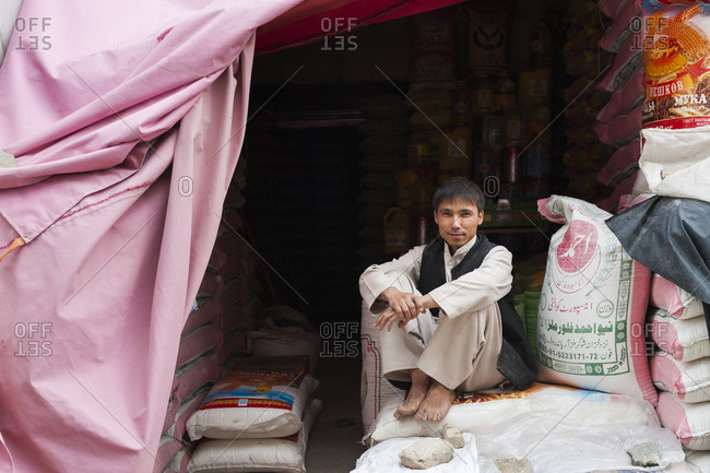 Kabul, Afghanistan - June 11, 2011: Young man sitting on sacks at a market
