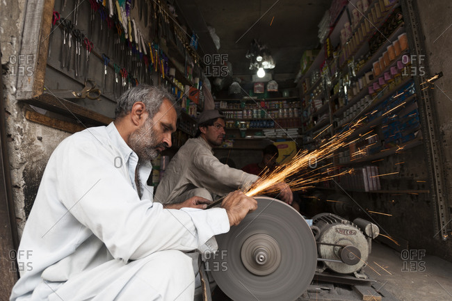 Kabul, Afghanistan - June 11, 2011: Two men working in a shop and using a grinding wheel