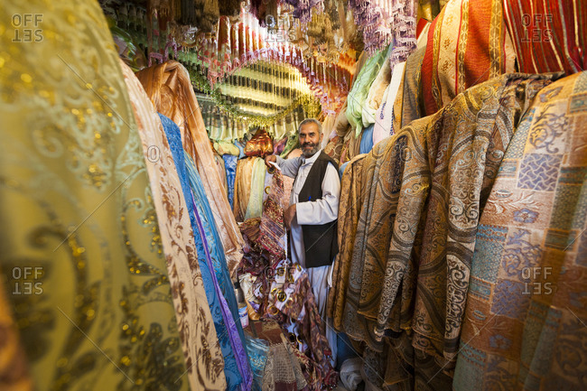 Kabul, Afghanistan - June 11, 2011: A man standing among a jumble of colors at a fabric bazaar