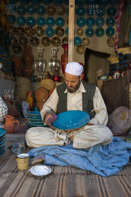 Istalif, Afghanistan - June 15, 2011: A man working in a shop famous for its handmade glazed clay plates and pots