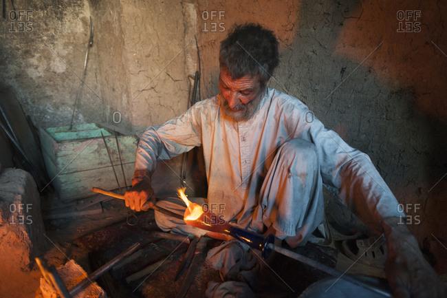 A glass blower works on a piece a blue Herat glass