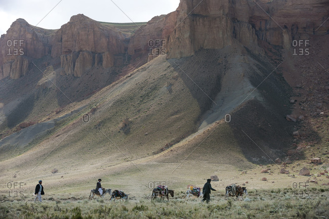 Bamyan Province, Afghanistan - June 21, 2011: Donkeys and farmers make their way home near Band-e Amir in Afghanistan
