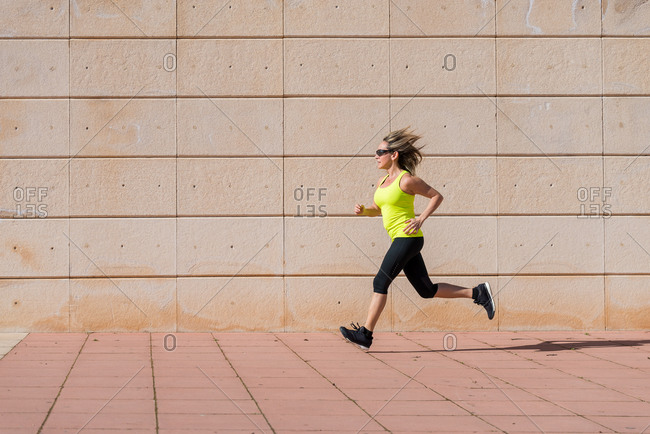 Image of adult woman running along white pattern wall while doing workout in morning