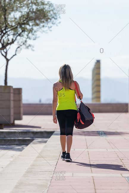 Rear view of a mid adult cheerful sporty woman with sports bag on shoulders walking outdoors