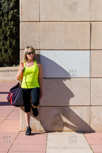 Blond mid adult sporty woman with sunglasses holding shoulder bag while leaning on wall and looking away