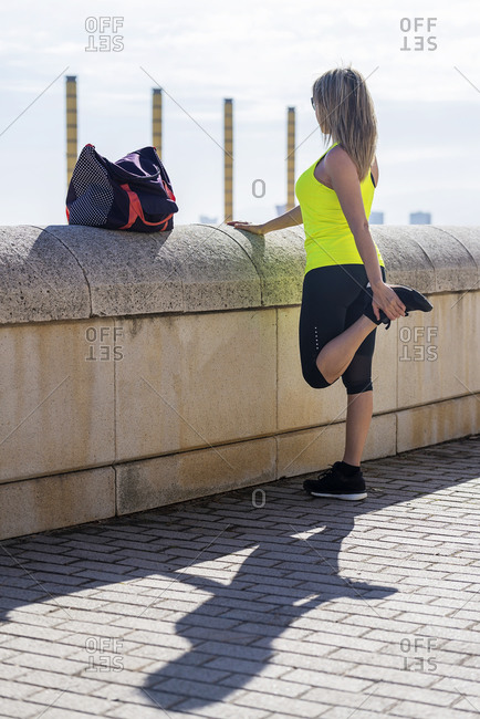Long haired fitness woman stretching outdoors before running