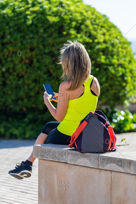 fit sport adult woman looking at mobile phone internet app tracking performance after running workout sitting on bench