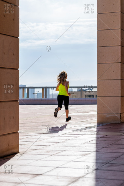 Long haired woman running in the city the morning. Sporty girl jogging along