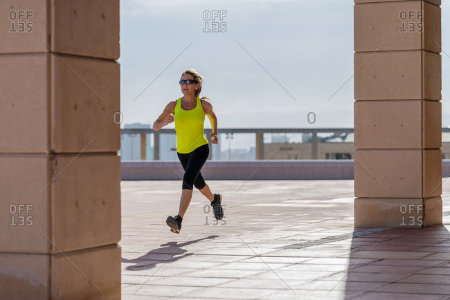 Long haired woman with sunglasses running in the city the morning. Sporty girl jogging along
