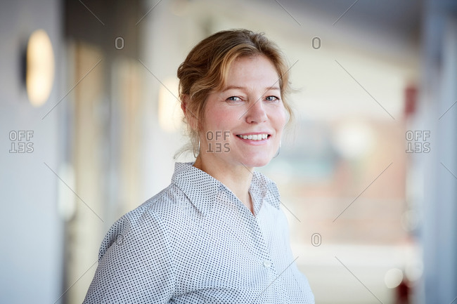Portrait of smiling mature entrepreneur standing at workplace