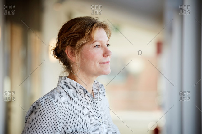 Confident female entrepreneur looking away while standing at workplace