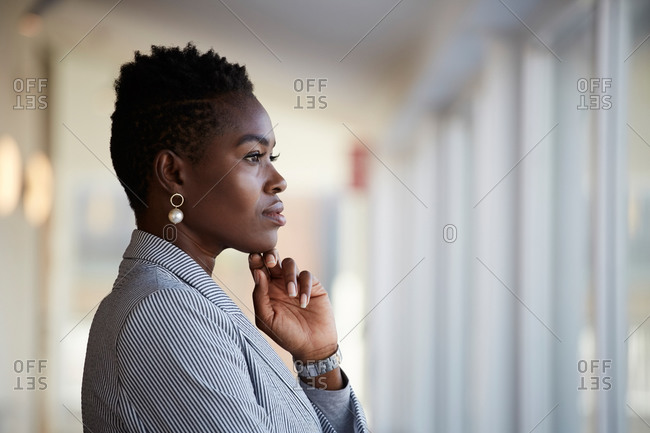 Side view of confident female entrepreneur looking away while standing at workplace