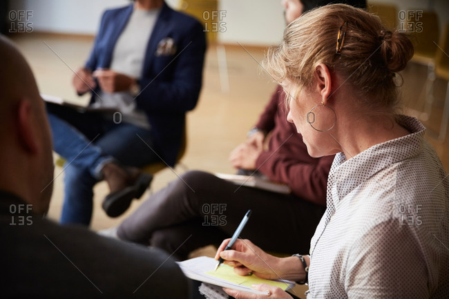 Female entrepreneur writing in book while sitting by male colleagues during office seminar