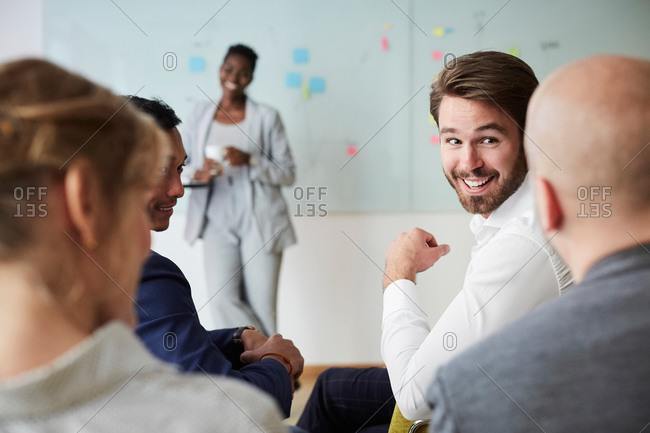 Smiling businessman looking at male colleague during presentation while sitting in office seminar