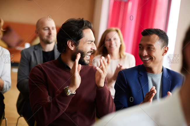 Smiling male and female entrepreneurs clapping while attending office seminar