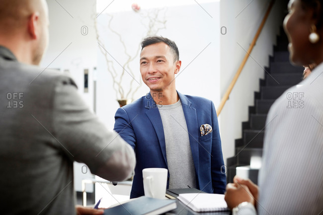 Smiling entrepreneur shaking hands with businessman in office