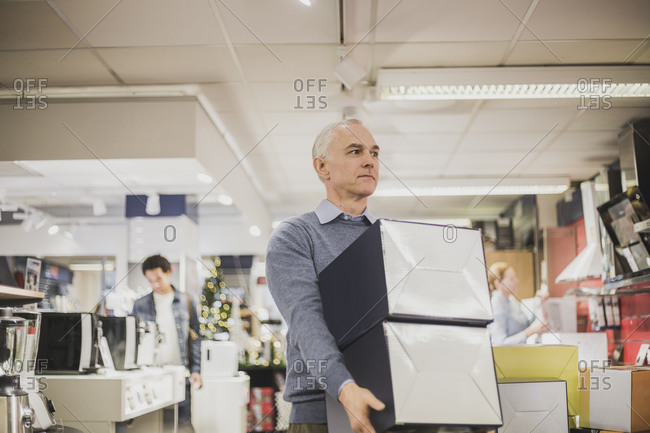 Mature salesman with boxes looking away while walking in electronics store