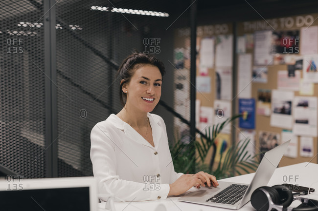 Portrait of smiling mid adult business professional using laptop at creative office