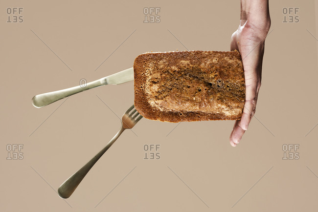 Man holding in his hand a homemade sponge cake with a fork and a spoon, on a brown background