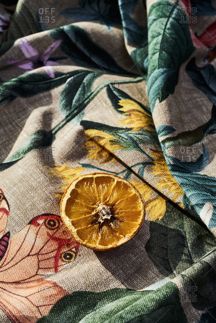 Half rotten orange on a wrinkled floral-patterned fabric