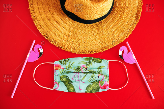 Straw hat and handmade summer mask, on red background.
