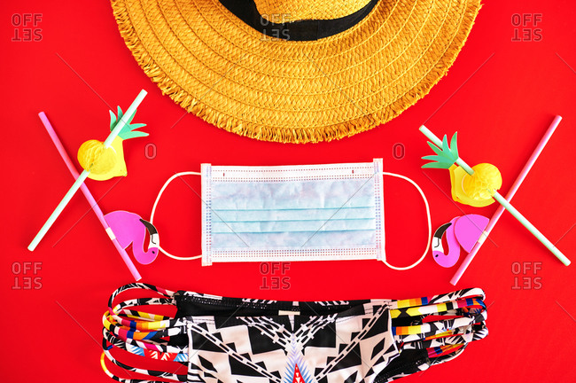 Hat and bikini next to surgical mask, on red background.