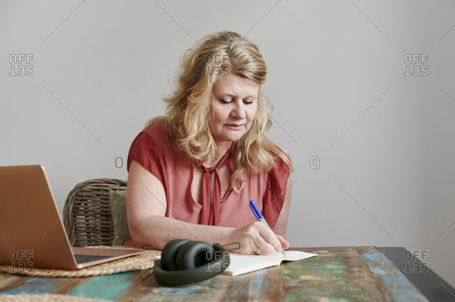 Mature woman sitting alone at a table in her home writing in a notebook and working on a laptop