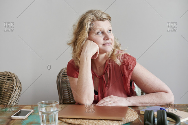 Mature woman sitting alone at a table and looking out through a window while working from home