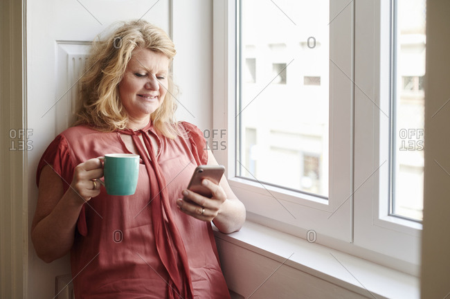Smiling mature woman leaning against a wall by a window drinking a cup of coffee and reading a text message