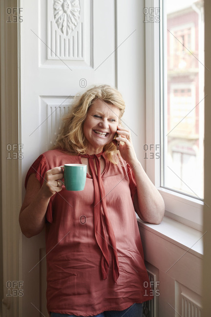 Smiling mature woman leaning against a wall by a window drinking a cup of coffee and talking on her cellphone