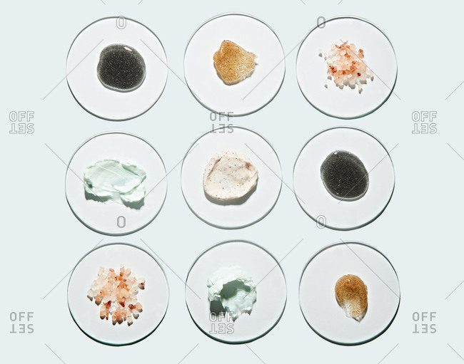 Overhead view of different types of skincare products on glass