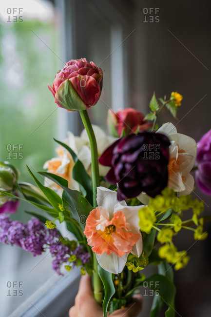Hand holding bouquet of spring flowers inside home