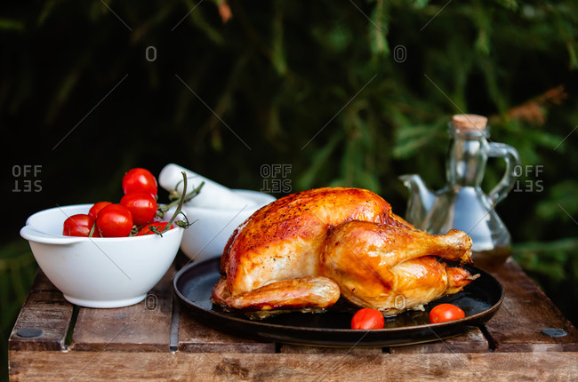 Fried chicken drizzled with olive oil and tomatoes near a fir tree