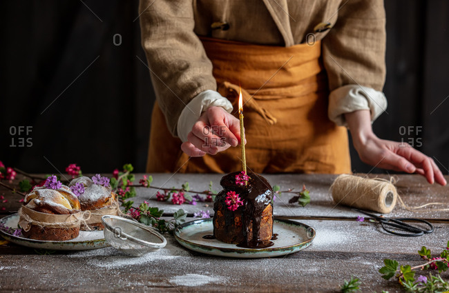 Woman is decorating orthodox Easter cake with chocolate