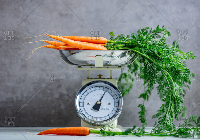 Carrots and vintage scale on grey background