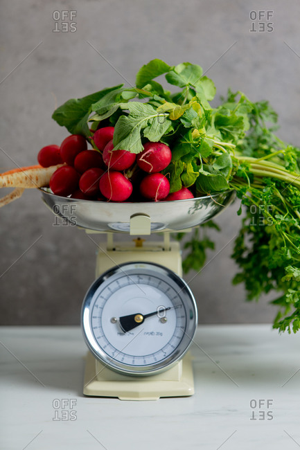 Radish, parsley and carrot on vintage market scale