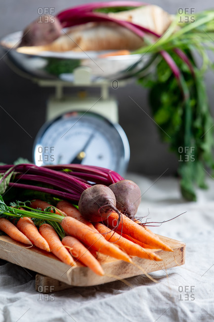 Carrots, beets and vintage scale on background