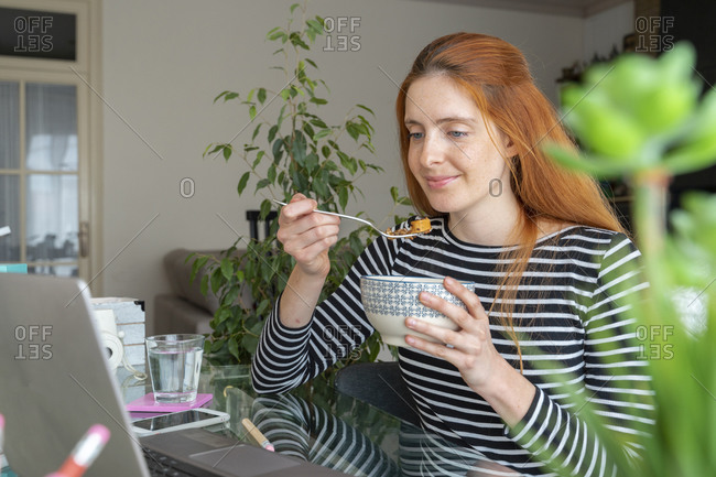 Young woman having breakfast and using laptop at desk at home