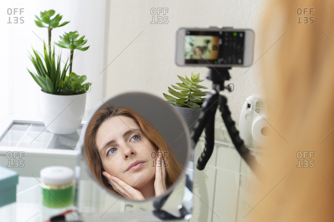 Young woman filming her beauty routine at home