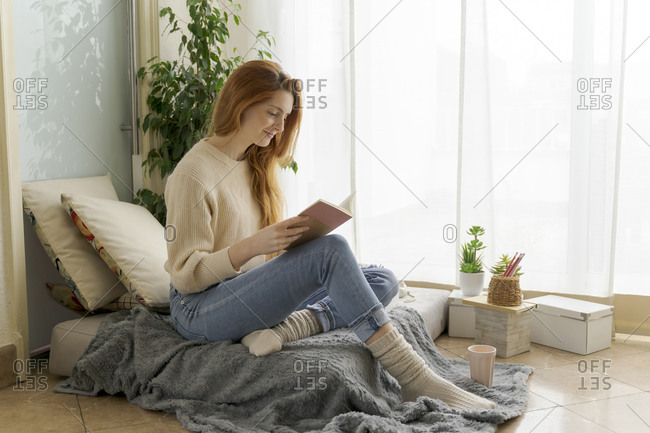 Young woman reading notebook at home