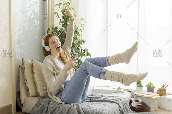 Carefree young woman listening to music with headphones at home