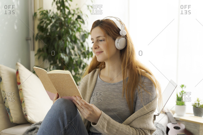 Young woman wearing headphones and reading notebook at home