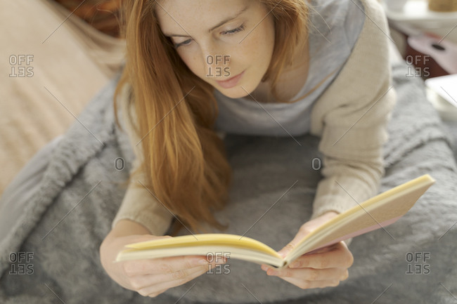 Young woman lying on blanket reading notebook